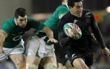New Zealand's full back Mils Muliaina (R) evades a tackle at Aviva Stadium in Dublin on 20 November 2010. Picture: Peter Muhly/AFP