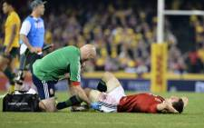 DOWN & OUT: British & Irish Lions captain Sam Warburton gets treated for an injury during the second test against Australia. Picture: AFP