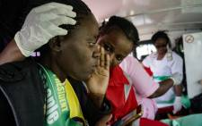 A paramedic attends to an injured Zanu-PF supporter inside an ambulance on the way to Mpilo hospital on 23 June 2018 in Bulawayo, Zimbabwe, after a bomb blast at a campaign rally at White City stadium. Picture: AFP.