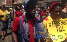 "A student shouts ""free water"" as peers keep each other hydrated in blazing heat in Pretoria during the Fees Must Fall march. They're making their way to the Union Buildings where President Jacob Zuma will be addressing student leaders and vice-chancellors. Picture: EWN."