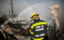 A fireman mans a hose during a fire in Barcelona informal settlement in Gugulethu, Cape Town. Picture: Thomas Holder/EWN