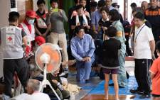 Japan's Prime Minister Shinzo Abe (C) visits a shelter for people affected by the recent flooding in Mabi, Okayama prefecture on 11 July, 2018. Picture: AFP