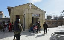 FILE: Pakistani security personnel rescue an injured woman after suicide bombers attacked a Methodist church during a Sunday service in Quetta on 17 December, 2017. Picture: AFP.