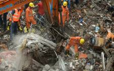 Indian rescue workers and fire officials look for survivors in debris at the site of a building collapse in Mumbai on 25 July 2017. Picture: AFP