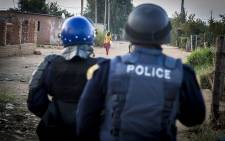 A young man with a golf club taunts police as they search through the streets of Lichtenburg in the North West for protesters following unrest in the area over service delivery. Picture: Reinart Toerien/EWN