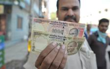 FILE: An Indian man display the currency of 500 and 1,000 rupees in Hyderabad on November 9, 2016. Picture: AFP.
