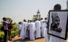 A family member carries a portrait of Rwanda's last King, late King Kigeli V Ndahindurwa, while others carry the coffin of the King to the King's Palace in Nyanza where the funeral services took place on this 15 January 2017. King Kigeli died in October, aged 80, in the United States. He had been living in exile in the suburbs of Washington since 1992. Picture: AFP