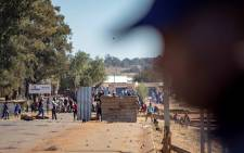 A protester hurls a stone towards a police line on a bridge spanning the R59 outside Sicelo informal settlement in Meyerton on 18 June 2018.  Picture: Thomas Holder/EWN.