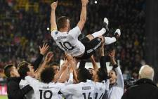 Teammates throw Germany's midfielder Lukas Podolski in the air after the friendly football match of Germany vs England in Dortmund, western Germany, on 22 March, 2017. It was Lukas Podolski's last match with the German team. Picture: AFP.