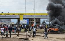 Supporters of opposition coalition the National Super Alliance stand next to tyres on fire in Kisumu, western Kenya, on 13 October 2017 during a protest against the re-run of the presidential election. Picture: AFP