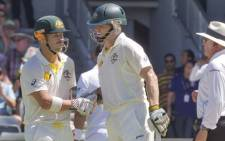 Australian batsman David Warner (L) is congratulated by fellow opening batsman Chris Rogers (C) on scoring 50 runs against England on the third day of the third Ashes cricket Test match in Perth on December 15, 2013. Picture: AFP.