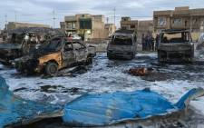 A picture taken with a mobile phone on February 16, 2017 shows burnt vehicles at the scene of a blast by a massive car bomb, which killed dozens in a used car market in southern Baghdad. Picture: AFP