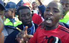An EFF supporter is rescued by police from ANC supporters who were assaulting him at TUT in Soshanguve. Picture: Vumani Mkhize/EWN.