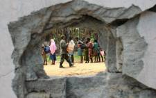 A Sri Lankan soldier is seen through a blast hole as he hands out food rations to displaced Tamil civilians at Puthumathalan on April 24, 2009. Picture: AFP