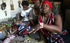 "Agnes Gaobepe, 36, a sangoma working in Wattville, a township of Benoni, gestures on 09 September 2004. ""Under apartheid, we were referred to as witch doctors, which is something that is opposite to what we do. We are traditional herbal healers, we concentrate on curing"" she says. Picture: AFP."