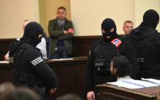 "Prime suspect in the November 2015 Paris attacks Salah Abdeslam (L) sits as he surrounded by Belgian special police officers in the courtroom at the ""Palais de Justice"" courthouse in Brussels for the opening of his trial, on 5 February, 2018. Picture: AFP"