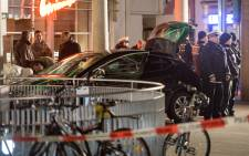 Police officers stand around a car in front of a business building in Heidelberg, western Germany, where a man ploughed into pedestrians before being shot by the police on 25 February, 2017. Picture: AFP.