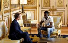 French President Emmanuel Macron speaks with Mamoudou Gassama, 22, from Mali, at the presidential Elysee Palace in Paris, on 28 May 2018. Picture: AFP.