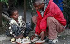 An Oromo girl sits next to a man as they eat donated food on 4 October 2017, at a temporary camp for displaced people outside Adama, Ethiopia. Picture: AFP.