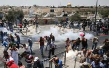 Palestinian worshippers run for cover from teargas fired by Israeli forces outside Jerusalem's Old City in front of the Al-Aqsa mosque compound on 21 July 2017. Picture: AFP.