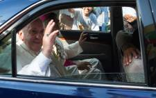 FILE: Pope Francis waves to well-wishers as he is driven through the streets of downtown Yangon on 27 November 2017. Picture: AFP.