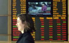 A woman walks past a stock exchange board. Picture: AFP.