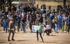 Students at Wits throw bricks at private security stationed outside Senate House during FeesMustFall protests. Picture: Thomas Holder/EWN