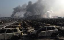 Smoke billows behind rows of burnt out Volkswagen cars at the site of a series of explosions in Tianjin, northern China on 13 August, 2015. Picture: AFP.