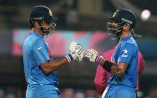 India's captain Mahendra Singh Dhoni and teammate Virat Kohli speak during the World T20 cricket tournament match between India and Pakistan at The Eden Gardens Cricket Stadium in Kolkata on 19 March, 2016. Picture: AFP.
