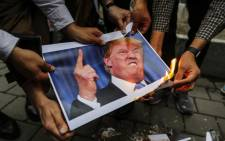 Iranians burn an image of US President Donald Trump during an anti-US demonstration outside the former US embassy headquarters in the capital Tehran on 9 May 2018 after Trump's withdrawal from the nuclear deal with Iran. Picture: AFP.