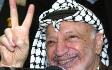"Palestinian leader Yasser Arafat waves the 'V' sign for victory during a reception to mark the anniversary of ""Fatah"" day outside of his West Bank Ramallah city legislative council buildings 31 December 2002, where he has been cooped up by Israeli forces for more than a year. Today marks the 38th anniversary of Arafat's Fatah movement's first failed guerrilla attack on Israel's National Water Carriers on January 1, 1965. Picture: AFP."