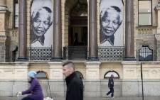 People walk past a banner with two pictures of Nelson Mandela as it hangs on the outside of the City Hall in 2013. Picture: AFP.