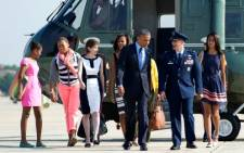 US President Barack Obama and his wife Michelle and children Sasha and Malia with their cousin Leslie Robinson get ready to depart on their African tour. Picture: AFP