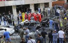 Onlookers watch as Lebanese rescue teams and security forces inspect the scene of a powerful blast in southern Beirut near the Iranian embassy. Picture: AFP.