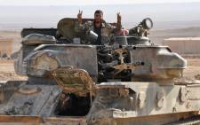 """A soldier from the Syrian government forces flashes the """"V"""" for victory sign in the eastern Syrian city of Deir Ezzor during an operation against Islamic State (IS) group jihadists on 2 November 2017. Picture: AFP."""