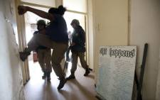 A member of the Tshwane Metro Police kicks open a door inside a residence of the Schubart Park block of flats during evictions. Picture: Sapa