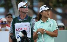 Lydia Ko of New Zealand stands with her caddie Gary Matthews and bag on the first hole during the final round of the LPGA LOTTE Championship Presented By Hershey at Ko Olina Golf Club on 15 April 2017 in Kapolei, Hawaii. Picture: AFP