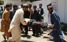 Afghan men carry a victim of a powerful car bomb in Lashkar Gah, the capital of Helmand province, on 22 June 2017. Picture: AFP