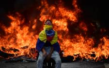 A Venezuelan opposition activist is backdropped by a burning barricade during a demonstration against President Nicolas Maduro in Caracas, on 24 April, 2017.