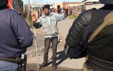 A Phumlani Village resident stands in front of Public order police, asking them not to shoot. Picture: Bertram Malgas