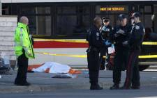 Police officers stand near one of the bodies on the street after a truck drove up on the curb and hit several pedestrians in Toronto, Ontario on April 23, 2018.