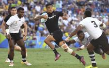 New Zealand's Regan Ware (C) evades a tackle to score a try during the men's rugby sevens gold medal match against Fiji at the Robina Stadium during the 2018 Gold Coast Commonwealth Games on the Gold Coast on 15 April  2018. Picture: AFP.