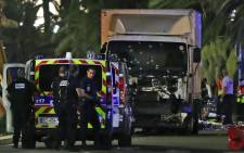 Police officers stand near a truck, with its windscreen riddled with bullets, which ploughed into a crowd leaving a fireworks display in the French Riviera town of Nice on 14 July 2016. Picture: AFP.