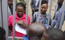 Commissioners of the Independent Electoral and Boundaries Commission (IEBC) Roselyn Akombe Kwamboka (2nd R) with Margaret Wanjala (2nd L) receive a petition from members of Kenya's civil society demonstrating at the entrance to the IEBC in Nairobi on 13 September 2017. Picture: AFP