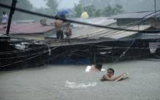 Residents try to cross through floodwaters as others wait on the roofs of their houses after a river overflowed in Manila. Picture: AFP.