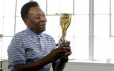 Brazilian soccer player Pele poses for a portrait with his 1958 World Cup trophy during an interview in New York in April 2016. Picture: Reuters/Action Images