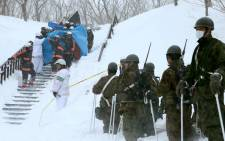 Firefighters carry a survivor rescued from the site of an avalanche in Nasu town, Tochigi prefecture, on 27 March, 2017, while Self Defense Force personnel look on. Picture: AFP.