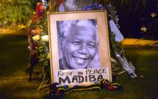 FILE: A file photo taken on 6 December, 2013 shows a framed image of former South African president Nelson Mandela as people pay tributes following his death, in Johannesburg. Picture: AFP.