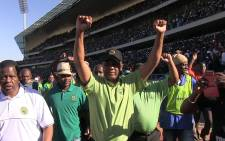 The Association of Mineworkers and Construction Union (Amcu) leader Joseph Mathunjwa raises his hands triumphantly in the Royal Bafokeng stadium near Rustenburg as miners agree to sign a wage agreement which ended the longest strike in South African history on 23 June 2014. Picture: Reinart Toerien/EWN