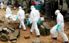 FILE: Liberian nurses carry the body of a suspected victim of Ebola at the Sonuwein community in Monrovia, Liberia, 3 October 2014. Picture: EPA/Ahmed Jallanzo.